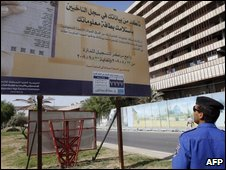 An Iraqi policeman reads an electocal committe information billboard urging people to update their voting record in Baghdad