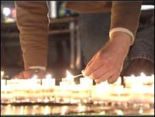 Man lights candles at an anti-hate crime vigil