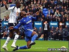Jlloyd Samuel brings Didier Drogba down