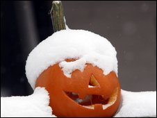 A snow-covered pumpkin lantern sits outside a home in Denver, Colorado