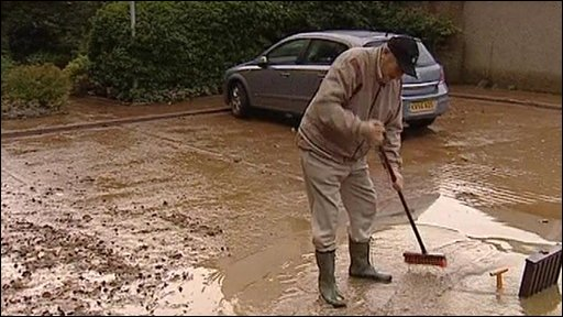 A resident attempts to clear flood water