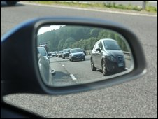 Queue of cars can be seen reflected in the wing mirror of a car - copyright BBC / Jeff Overs
