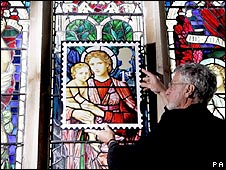 Reverend Neil Spencer holds a blown-up stamp in front of the Henry Holiday stained glass window at St Michael church in Ormesby, Norfolk.