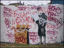 Defaced banksy mural