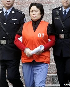 Xie Caiping is led away from court in Chongqing, China (3 November 2009)