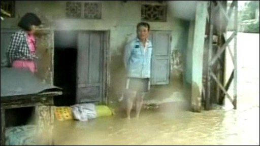 Vietnamese standing in water outside flooded home