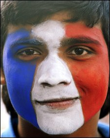 A French soccer fan his face painted in the colours of the French flag