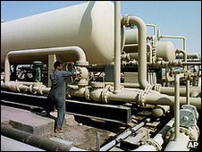 An Iraqi oil field worker checks pipes at the West Qurna oil field