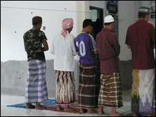 Men pray at mosque with bullet-riddled walls  in southern Thailand