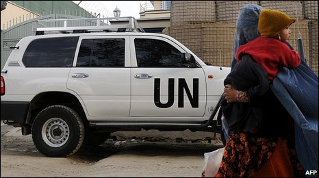 burqa-clad Afghan woman carries her child as she walks past a United Nations vehicle in Kabul on November 5, 2009