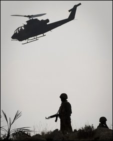 Pakistani soldiers secure an area as a Pakistani Army AH-1 Cobra attack helicopter flies past the top of Kund moutain near Kotkai village in South Waziristan on October 29, 2009