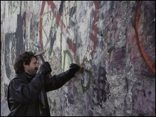 A man with a hammer chipping off the wall. Photo: Ronald Breze