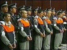 a line up of defendants (orange tops) next to security officers during a trial over the July, 2009 ethnic unrest  ( 15 Oct)