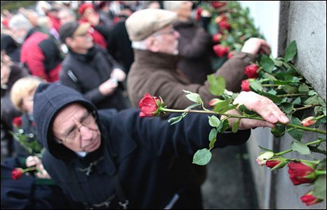 Visitors place roses into cracks in a still-existing section of the Berlin Wall on 9 November 2009