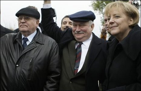 German Chancellor Angela Merkel (right), former Soviet leader Mikhail Gorbachev (left) and former Polish President Lech Walesa cross the Bornholmer Bridge in Berlin on 9 November 2009