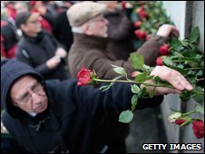 People place roses into cracks in a still-existing section of the Berlin Wall at the Bernauer Strasse memorial, 9 November 2009