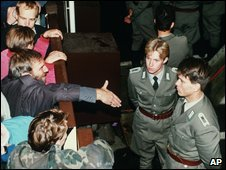 East German border policemen, right, refusing to shake hands with a Berliner at the Checkpoint Charlie border (November 10 1989)