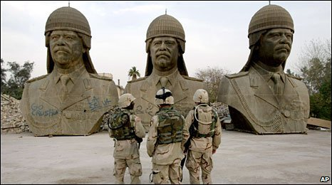 US soldiers stare at three busts of Saddam Hussein in Baghdad