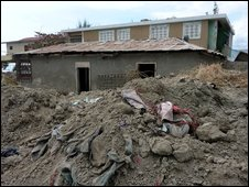 Houses in Gonaives remain dwarfed by mountains of mud