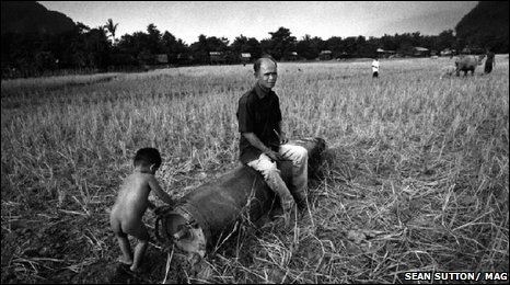 A farmer and his young son with a 2000lb shell case in a field