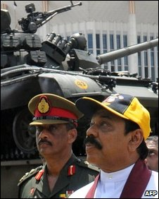 Sri Lankan President Mahinda Rajapaksa (C) and Chief of Defence Staff Sarath Fonseka (L) look at weapons captured from Tamil Tiger rebels in the capital Colombo on October 3, 2009.