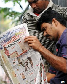 Sri Lankan men read a newspaper in Colombo on November 5, 2009