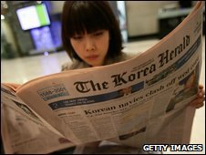 A woman reads a newspaper in Seoul on 10 November 2009