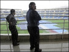 Officials watch ground staff cover the ground at the DY Patil stadium in Mumbai, India, Wednesday, Nov. 11, 2009.