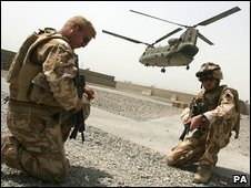 Troops kneel as a Chinook helicopter takes off in the background
