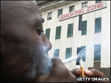 Kenyan office worker lights cigarette in a designated smoking area in Nairobi's central business district