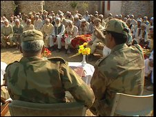Pakistani officers attend a meeting with locals