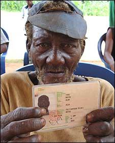 A Baka man in Cameroon holds up his civil registration (Photo: Plan)