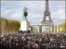 People gather near the Eiffel Tower, waiting for French marketing company Mailorama hostesses to deliver envelopes of cash , on November 14, 2009 at in Paris, as part of a French marketing company Mailorama advertising stunt