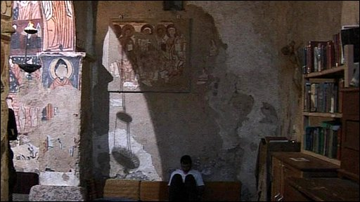 Man sitting in fresco-decorated ruined room of Deir Mar Musa monastery