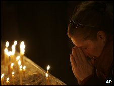 A woman prays inside St Sava church in Belgrade, after hearing of the patriarch's death