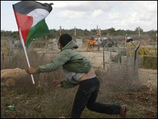 A Palestinian throws stones at Israeli security forces in the West Bank