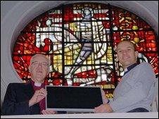 Lord Carey & Revd. Cowan display a PVC panel at the Church