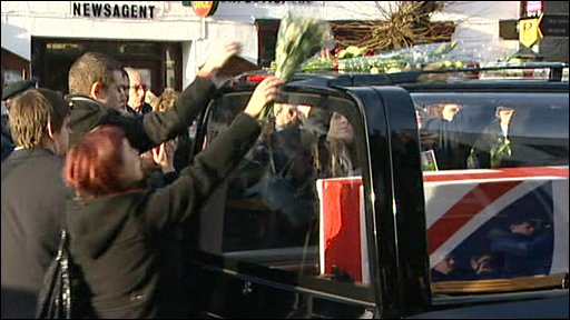 Floral tributes are paid as the cortege passes through Wootton Bassett