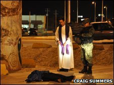A priest stands over the body of a murder victim