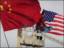 A worker hoists Chinese and US flags on Tiananmen Square, 16 November
