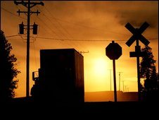 Silhouette of truck at railroad crossing
