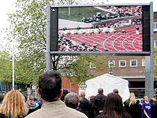 Image shows people in Castle Square watching a race on the Big Screen