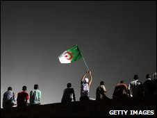 A Sudanese man waves an Algerian flag