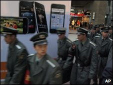 Chinese security guards walk past an advertisement for iPhone