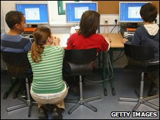 Teacher with three pupils using computers