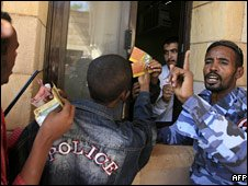 A Sudanese policeman controls a line of Egyptian and Sudanese fans as they try to get tickets for the World Cup