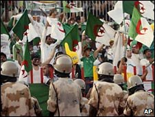 Sudanese riot police stand guard as Algerian fans cheer for their team in Khartoum. Photo: 18 November 2009