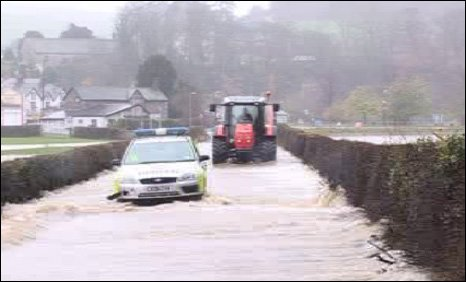 Police car and tractor with flood water