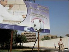 An Iraqi security walks past a billboard in Baghdad relating to the impending poll