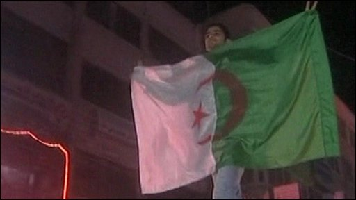 A man holds an Algerian flag 